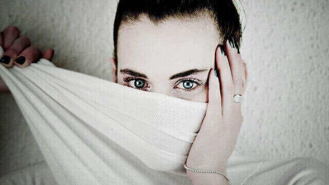 布で顔半分を隠す女性