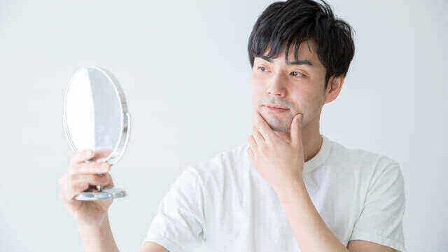 鏡を見ながら自分の肌質を触って確かめる男性